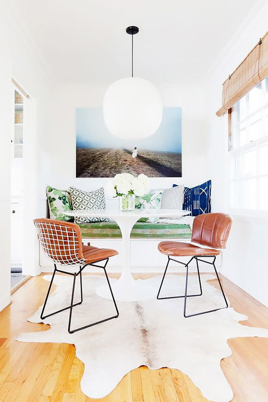 modern kitchen nook with upholstered bench,leather padded dining chairs, oversized art print and large pendant light fixture / sfgirlbybay
