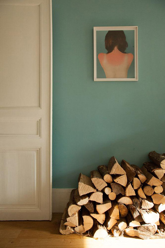 unique painting on bright blue wall with stacks of wood. / sfgirlbybay