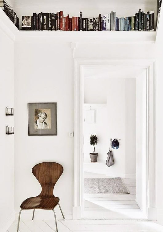 white book-lined room with vintage wood chair. / sfgirlbybay