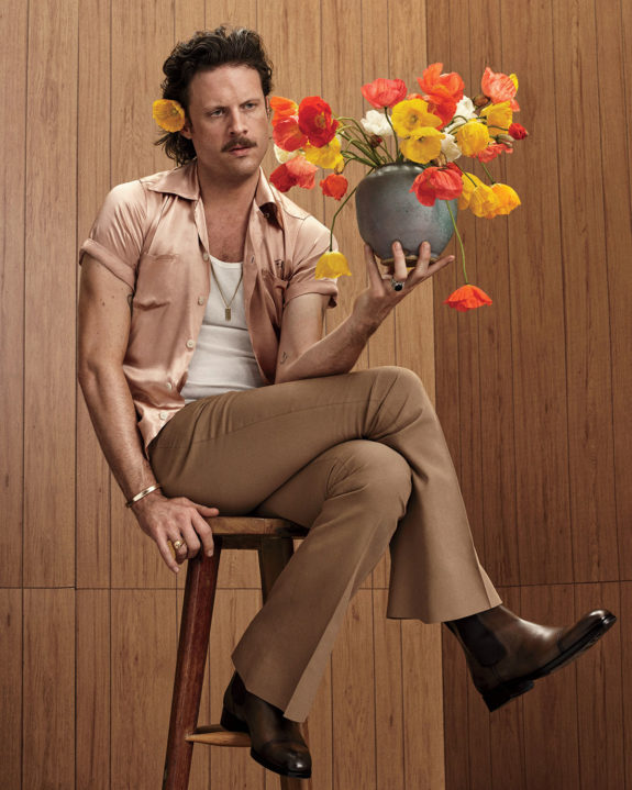 father john misty sitting on a stool holding a vase of flowers. / sfgirlbybay
