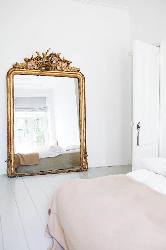whitewashed bedroom with oversized ornate gold mirror. / sfgirlbybay