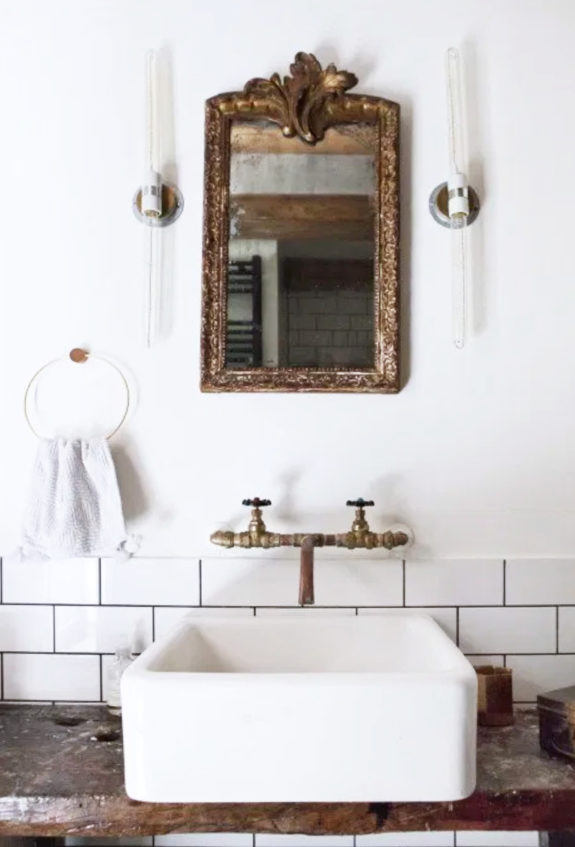 bathroom with modern wall lighting fixtures and sink mixed with vintage brass mirror and faucet. / sfgirlbybay