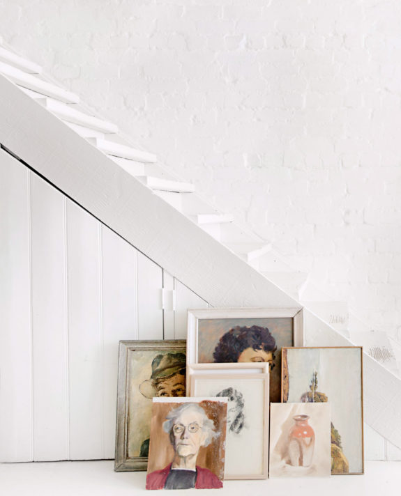 whitewashed interior with vintage portrait painting collection leaning on wall. / sfgirlbybay