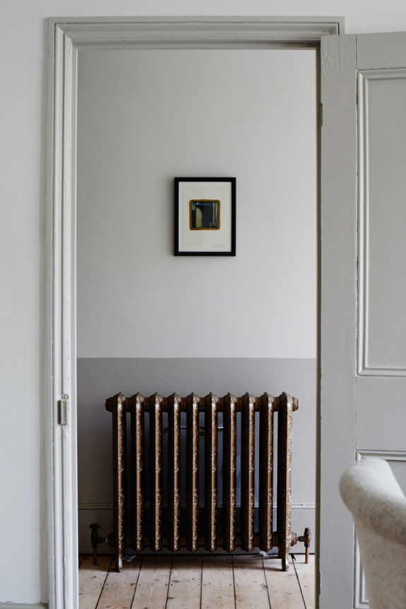 simple hallway with small framed painting above vintage radiator photographed by cassandra ellis. / sfgirlbybay