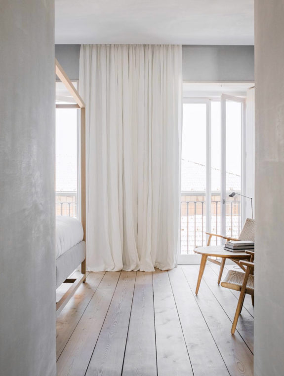 whitewashed interior with wood floors and floor to ceiling white drapery. / sfgirlbybay
