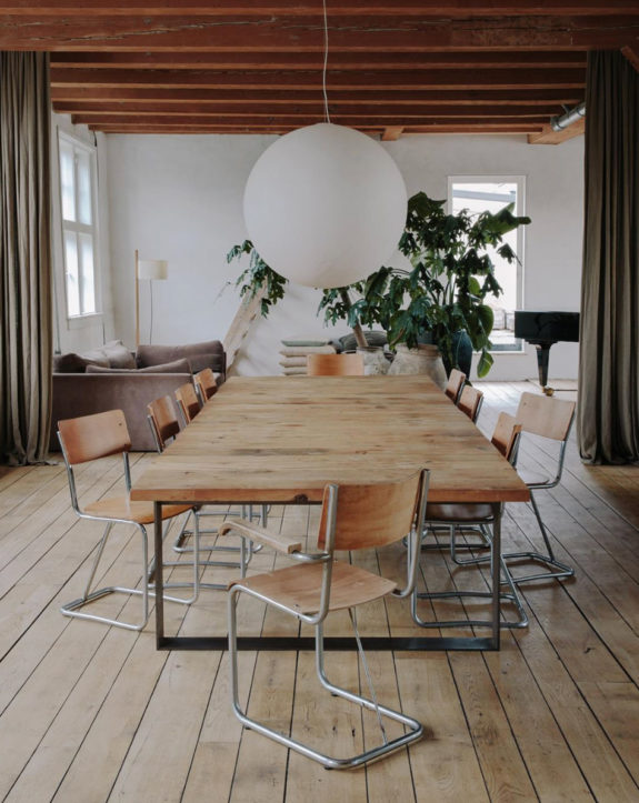 modern dining room with wood and metal table and chairs and large paper lantern. / sfgirlbybay